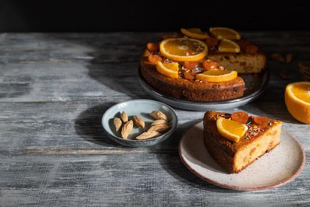 Oranje cake op een grijze houten achtergrond. hard licht. contrast, low key.