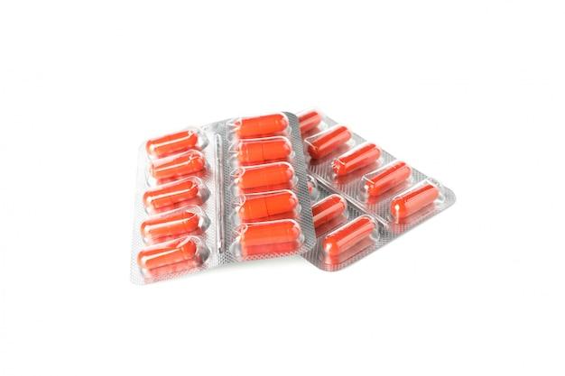 Oranje capsulespil in blaarpak dat op witte achtergrond wordt geïsoleerd