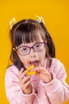 Oranje chips dragen. aantrekkelijk jongedame met psychische stoornis mond openen en chip erin stoppen