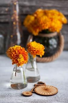 Oranje chrysant bloemen en houten fiets op rustieke tafel