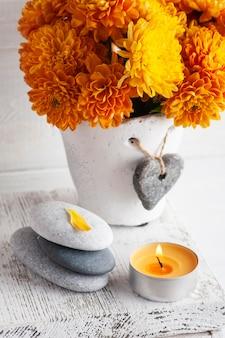 Oranje chrysant bloemen met kiezelstenen en aroma kaars op witte rustieke tafel