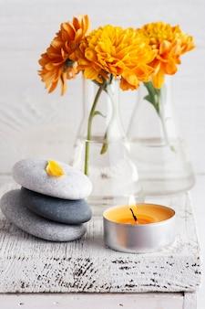 Oranje chrysant bloemen met kiezelstenen en aromakaars