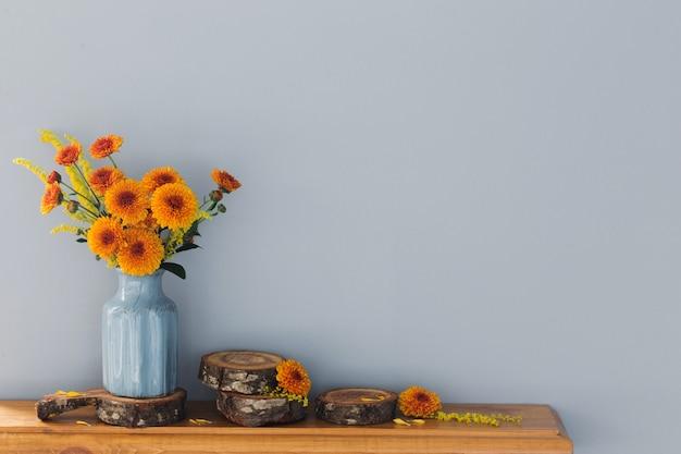Oranje chrysanten in blauwe vaas op houten plank op achtergrondmuur