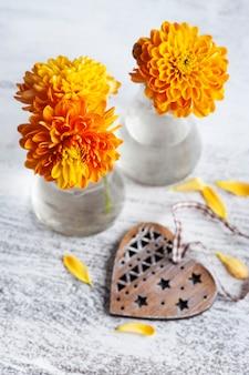 Oranje chrysantenbloemen en hart op rustieke achtergrond. wenskaart met kopie ruimte voor uw tekst