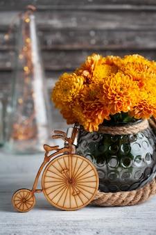 Oranje chrysantenbloemen en houten fiets op rustieke achtergrond. wenskaart met kopie ruimte voor uw tekst