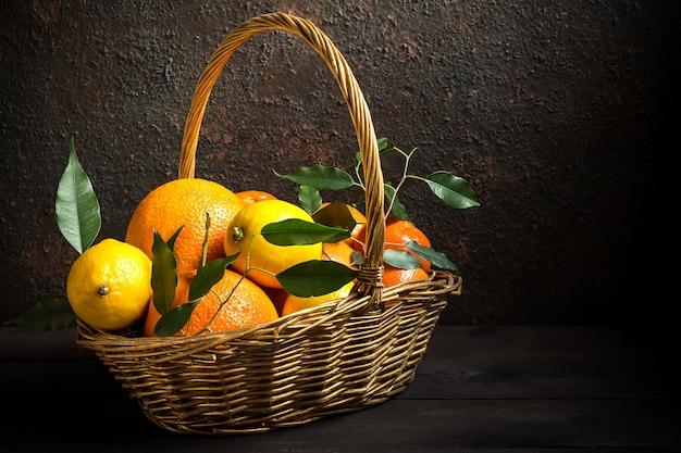 Oranje citroen citrusvruchten in een mand en sap op een donkere achtergrond, dieet gezonde voeding
