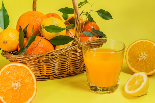 Oranje citroencitrusvruchten in een mand en een sap op een gele achtergrond, dieet gezond voedsel