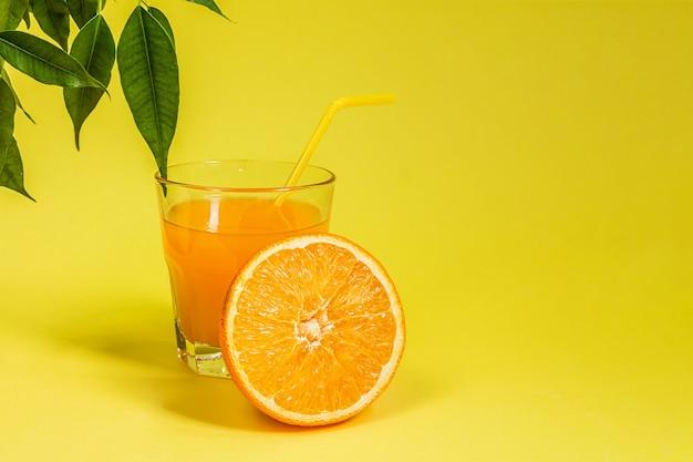 Oranje citroencitrusvruchten in een mand en een sap op een gele achtergrond