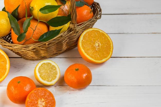 Oranje citroencitrusvruchten in een mand en een sap op een lichte achtergrond, dieet gezond voedsel