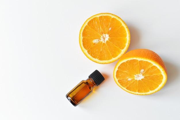 Oranje citrus etherische olie in donkere glazen fles met vers oranje fruit