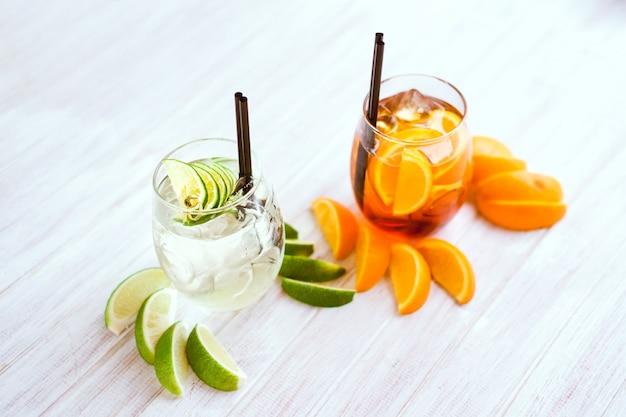 Oranje cocktail en ijsblokjes op witte achtergrond.