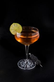 Oranje cocktail met citroenplak en braambessenbrochette op zwarte achtergrond