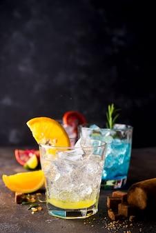 Oranje cocktail met ijs, blad van munt en oranje plak op zwarte steenachtergrond