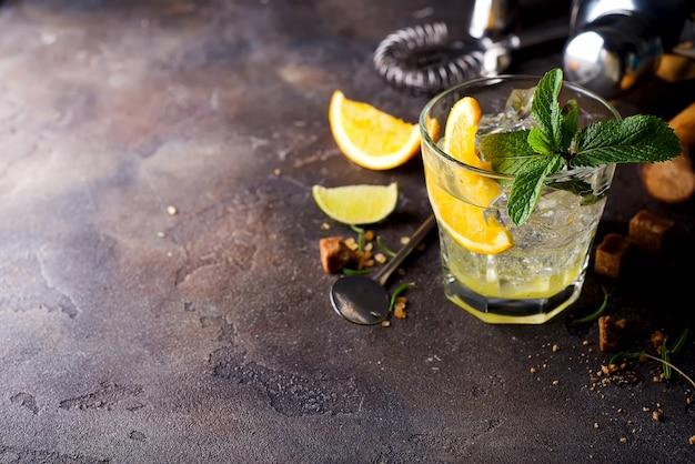 Oranje cocktail met ijs, blad van munt en oranje plak.