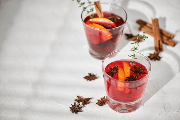 Oranje cocktail met rum, likeur, plakjes peer en tijm op witte tafel, selectieve focus