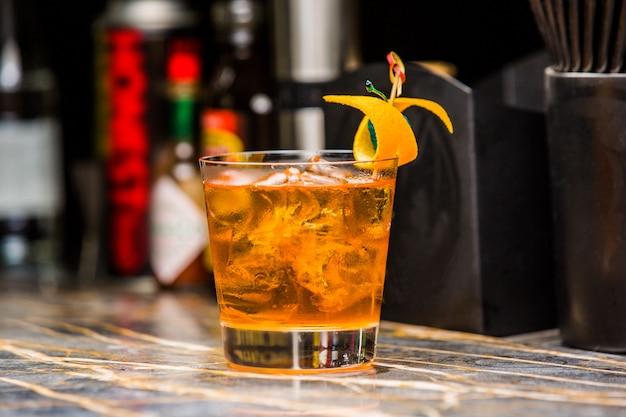 Oranje cocktail shot gegarneerd met sinaasappelschil
