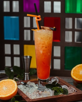 Oranje cocktailglas met pijp en gehakt ijsblokjes