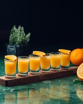 Oranje cocktails in kleine glazen.