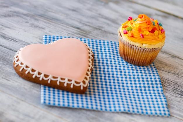 Oranje cupcake en hartkoekjes zoetwaren op blauw servet liefde is zin voor levenswonderen in eenvoud...
