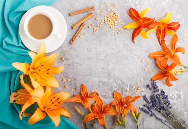 Oranje dag-lelie en lavendelbloemen en een kop van koffie op een grijze concrete achtergrond met blauwe textiel