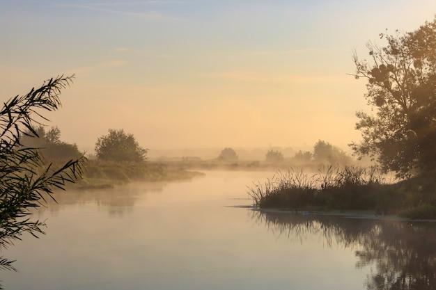 Oranje dageraad op de rivier in zonnige zomerochtend. rivierlandschap