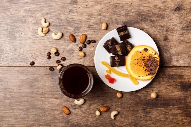 Oranje de kaneelkoffie en noten van het chocoladesuikergoed op hout