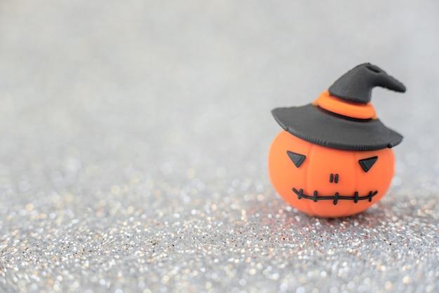 Oranje decoratieve pompoen op zilveren onscherpe achtergrond. halloween, minimalisme concept. groet, uitnodigingskaart. kopieer ruimte voor de tekst.