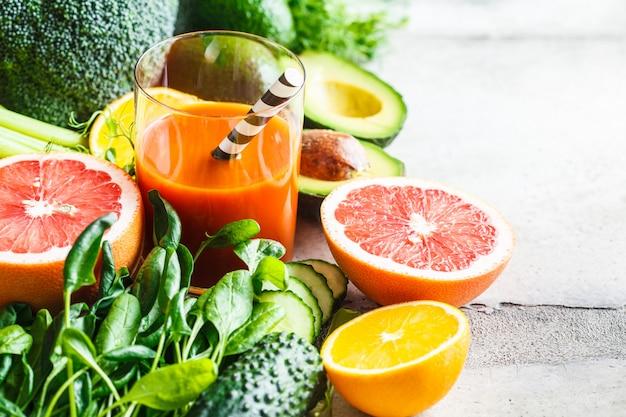 Oranje detox smoothie in glas. ingrediënten voor detox smoothie achtergrond.