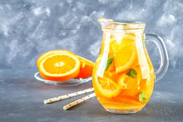 Oranje detoxwater in een waterkruik op een grijze concrete achtergrond. gezond eten, drinken.