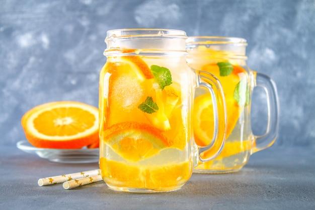 Oranje detoxwater in metselaarkruiken op een grijze concrete achtergrond. gezond eten, drinken.
