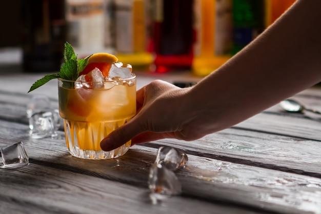 Oranje drank met ijs. hand met glas cocktail. je drankje is klaar. het originele recept van de barman.