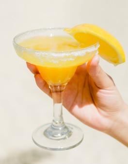 Oranje drankje in glas in de hand