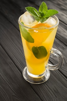 Oranje drankje of limonade met munt en ijs in het glas op de zwarte houten achtergrond. detailopname. locatie verticaal.