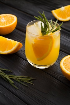 Oranje drankje of limonade met rozemarijn en ijs in het glas op de zwarte houten achtergrond. detailopname. locatie verticaal.