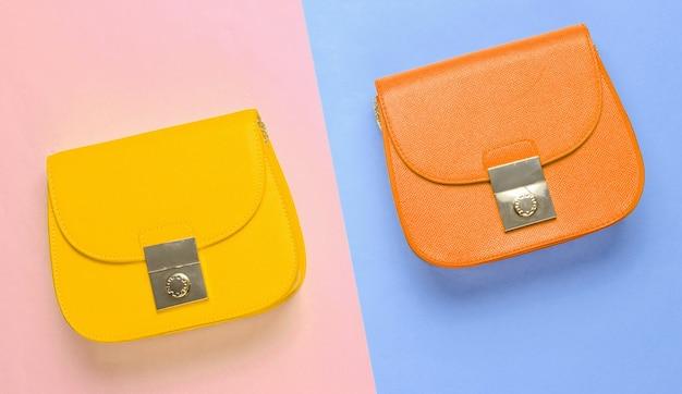 Oranje en gele leren mini-tassen op een pastelkleurige achtergrond. minimalisme mode-concept. bovenaanzicht