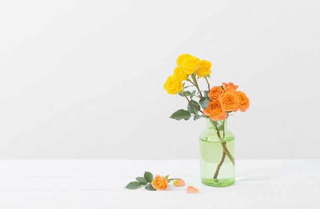 Oranje en gele rozen in glasvaas op wit
