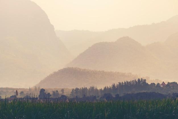 Oranje en gele zonsondergang met bergensilhouetten. achtergrond van de gradiënt de levendige aard