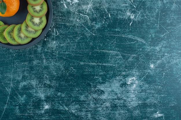 Oranje en gesneden kiwi in een pan, op de marmeren tafel.