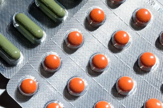 Oranje en groene pillen in een blisterverpakking liggen op een lichte achtergrond. grote iplan. uitzicht van boven