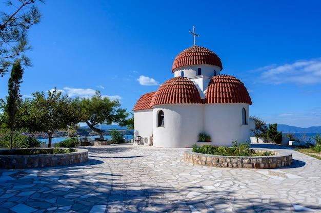 Oranje en witte kerk op heuvels van nea roda dorp en haven in halkidiki, griekenland