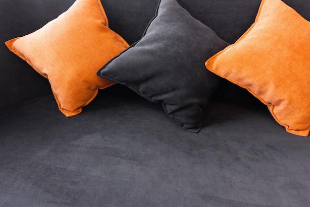 Oranje en zwarte kussens op de gestoffeerde bank. plaats om tekst in te voegen