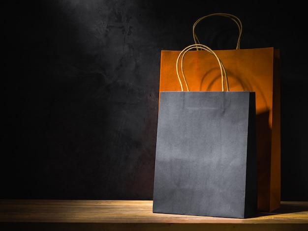 Oranje en zwarte papieren boodschappentassen op houten tafel