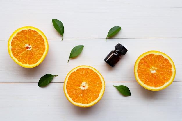 Oranje etherische olie met verse oranje citrusvruchten en groene bladeren op witte houten