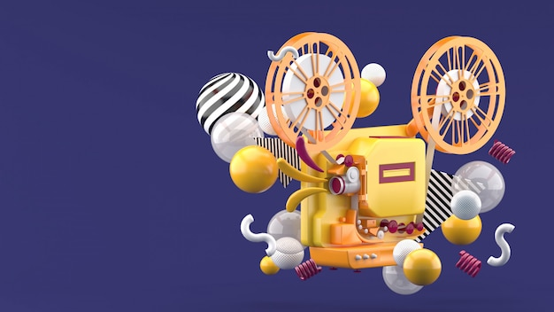 Oranje filmprojector temidden van kleurrijke ballen op paars. 3d render.