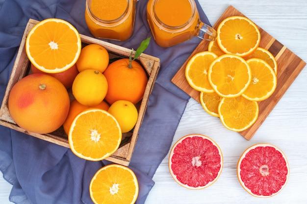 Oranje fruit concept jus d'orange grapefruit oranje fruit op houten snijplank op violette doek