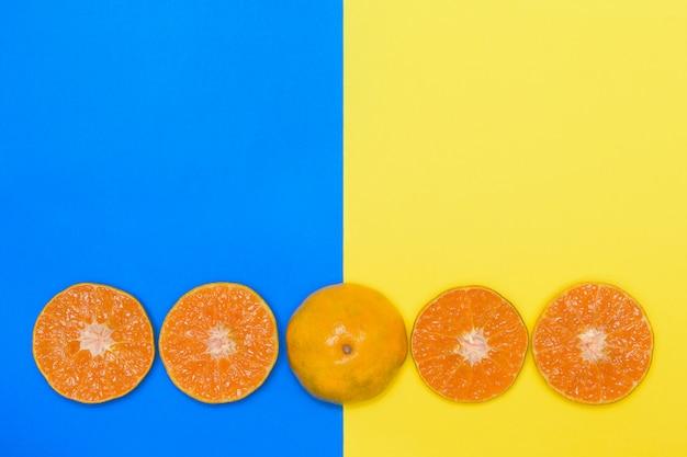 Oranje fruit dat half op blauwe en gele achtergronden wordt gesneden.