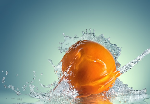 Oranje fruit en opspattend water op blauwe achtergrond met kleurovergang