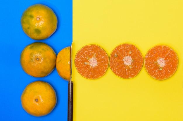 Oranje fruit en oranje half gesneden op blauwe en gele achtergronden.