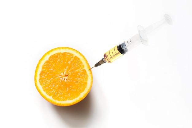 Oranje fruit en plastic wegwerpspuit. ronde plak geïsoleerd op wit. detailopname.