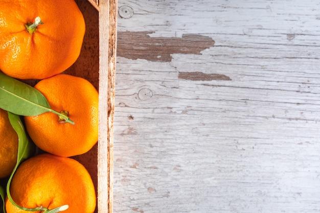 Oranje fruit in houten kist bovenaanzicht met kopie ruimte houten oppervlak